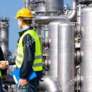 photo-two-petrochemical-contractors-closing-a-deal-in-front-of-an-oil-refinary-85912450